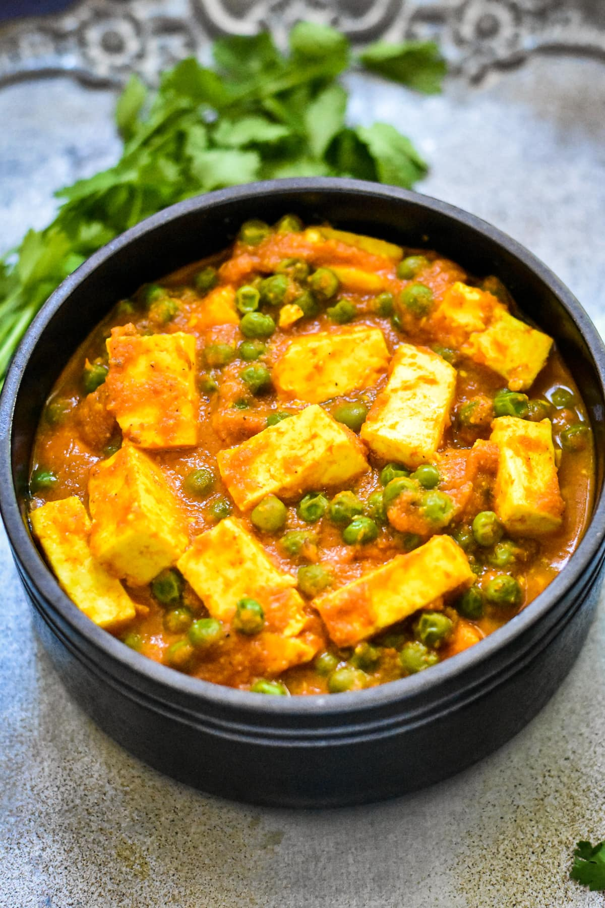 easy matar paneer recipe in black bowl with cilantro sprigs on silver platter
