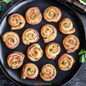 Samosa flavored puff pastry pinwheels on a black plate