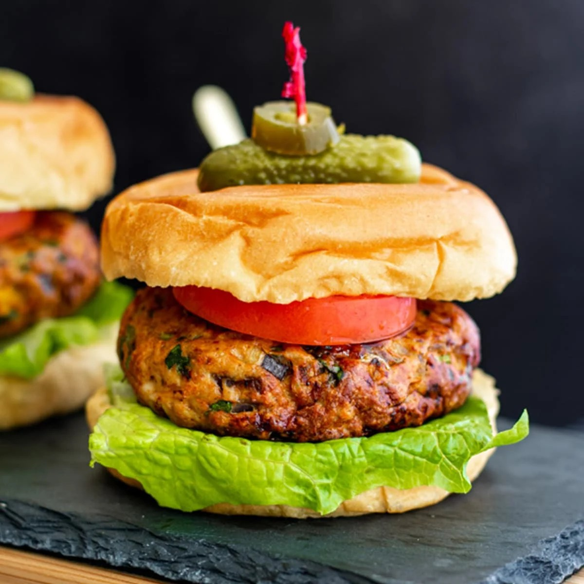 mexican style chicken burger on buns with lettuce, tomato and skewered with pickle