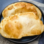 two pieces golden brown fried bhatura on black plate