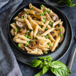 Creamy penne pasta in a black bowl