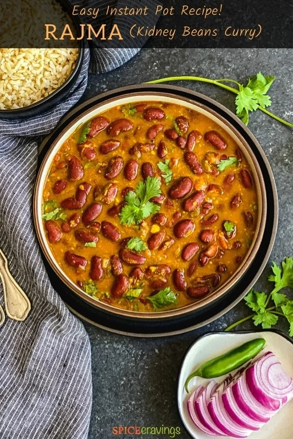 Kidney beans curry garnished with cilantro, next to brown rice and onions