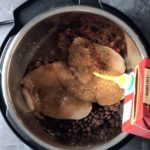 pouring chicken broth over chicken breasts and veggies in instant pot