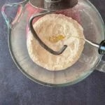 oil pouring into flour in bowl of stand mixer with dough hook