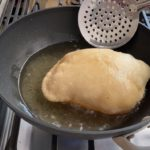 bhatura fry bread frying in hot oil on the stove