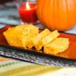 sliced pumpkin cornbread loaf on platter with pumpkin in background