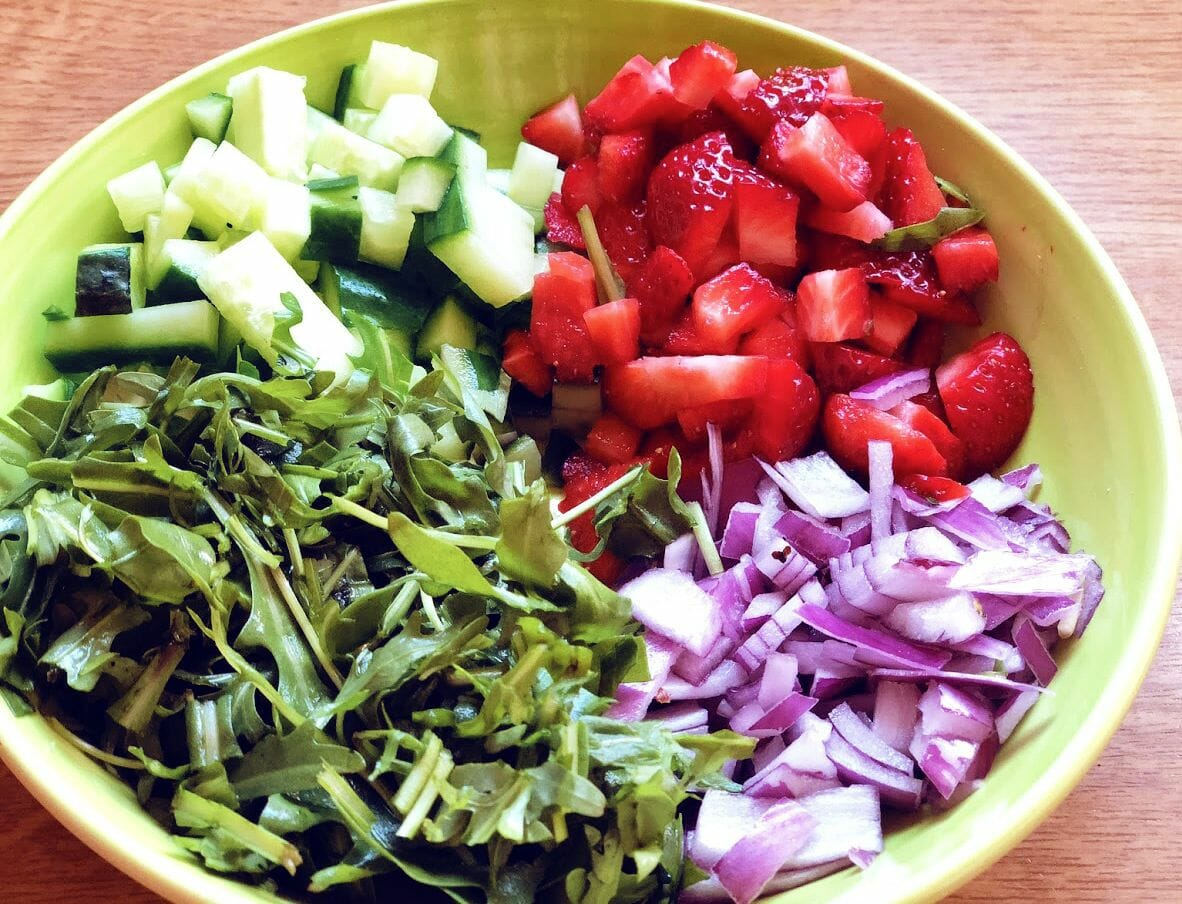 Chopped strawberries, cucumbers, aragula leaves and onions in a bowl