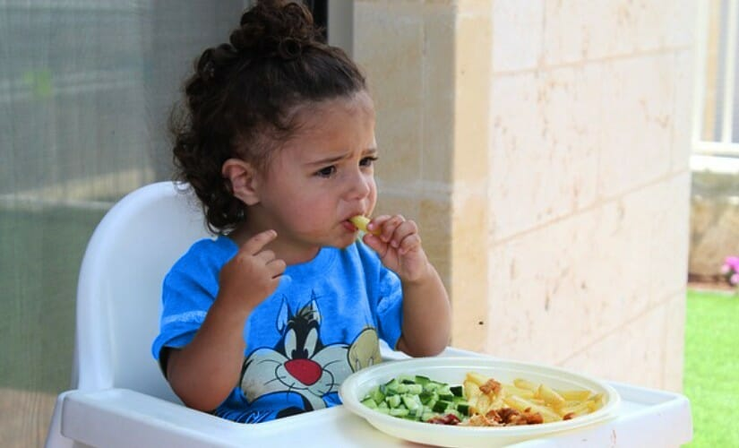 A Picky Eater Toddler sitting on a chair to eat