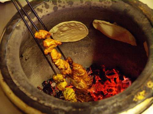 Cooking food in a Tandoori Indian Cooking method in a tandoor grill. Indian cooking method