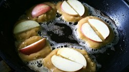 Transfer to a pastry bag or ziplock bag with the bottom edge cut off (REMINDER: cut off edge AFTER batter has been transferred to ziplock bag). Over medium/medium-high heat, heat oil in a non-stick frying pan and using pastry bag put 1-2 tbsp of batter into the oil. Place an apple slice or two on top of raw batter and press down.