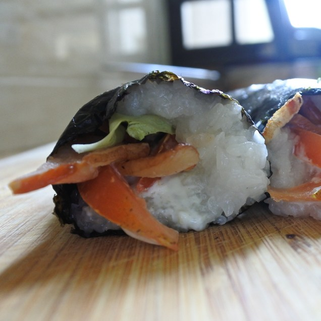 Once you get to the opposite end where the nori sheet is uncovered by rice, slightly moisten it with your fingers and continue rolling. The moistened seaweed will help 'seal' the sushi roll up.