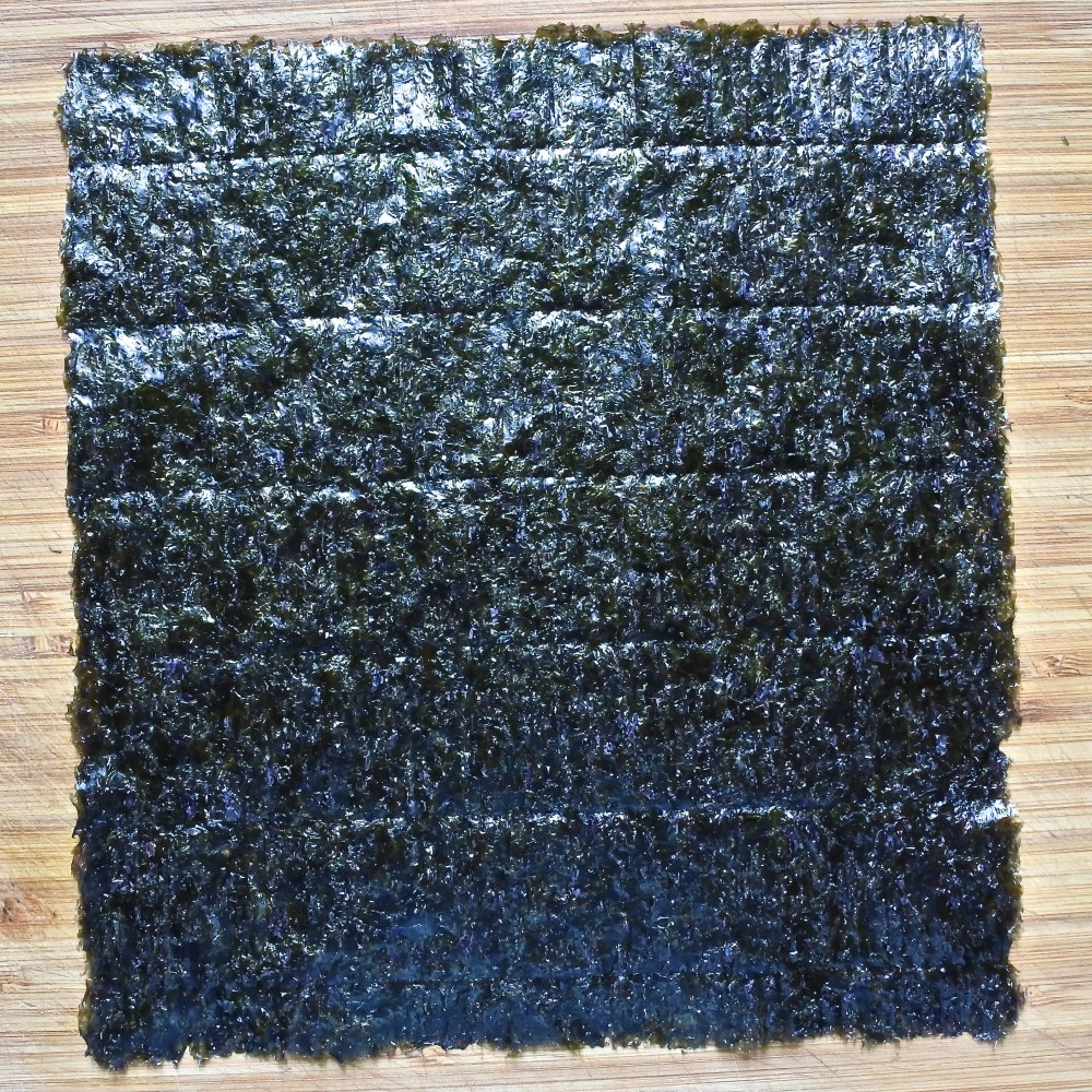 a sheet of nori seaweed on a wooden cutting board