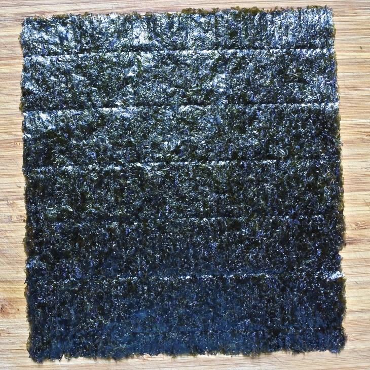 a sheet of nori seaweed on a wooden cutting board