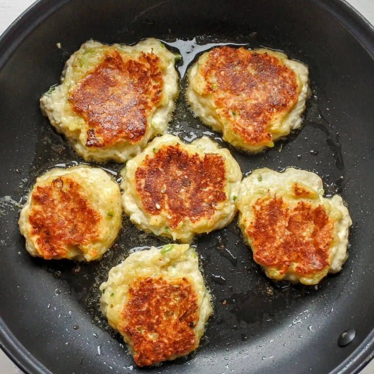 golden Indian cheese fritters frying in a pan