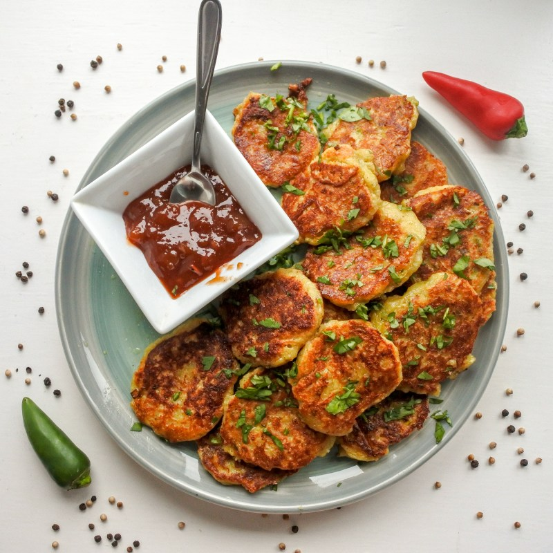 Indian spiced cheese fritters on a plate garnished with chopped cilantro, chutnery, chili peppers and spices
