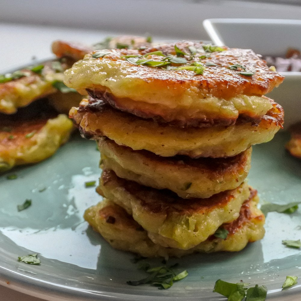 a stack of fritters on a plate garnished with chopped cilantro