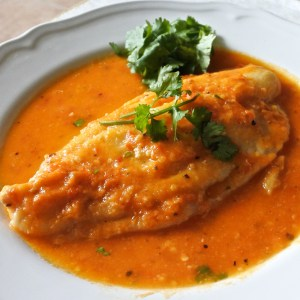 A boneless John Dory fillet smothered in a chile wine sauce on a plate garnished with cilantro