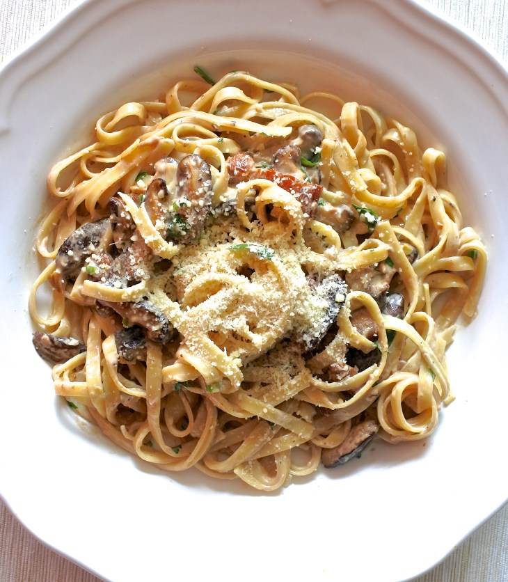 fettuccine tossed in cream sauce with mushrooms and pancetta garnished with Parmesan cheese
