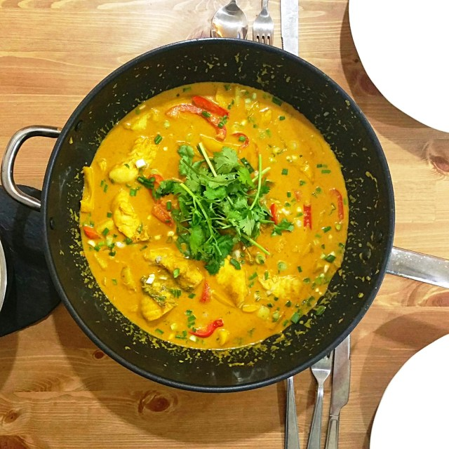 a big pot of white fish poached in Thai yellow curry with potatoes and red bell pepper