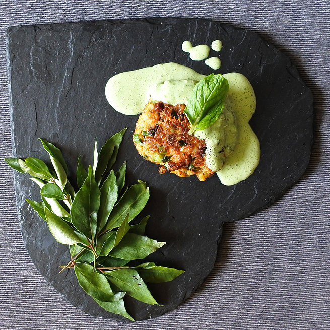 Indian spiced fish cakes drizzled with a mint yogurt sauce next to curry leaves on heart shaped slate