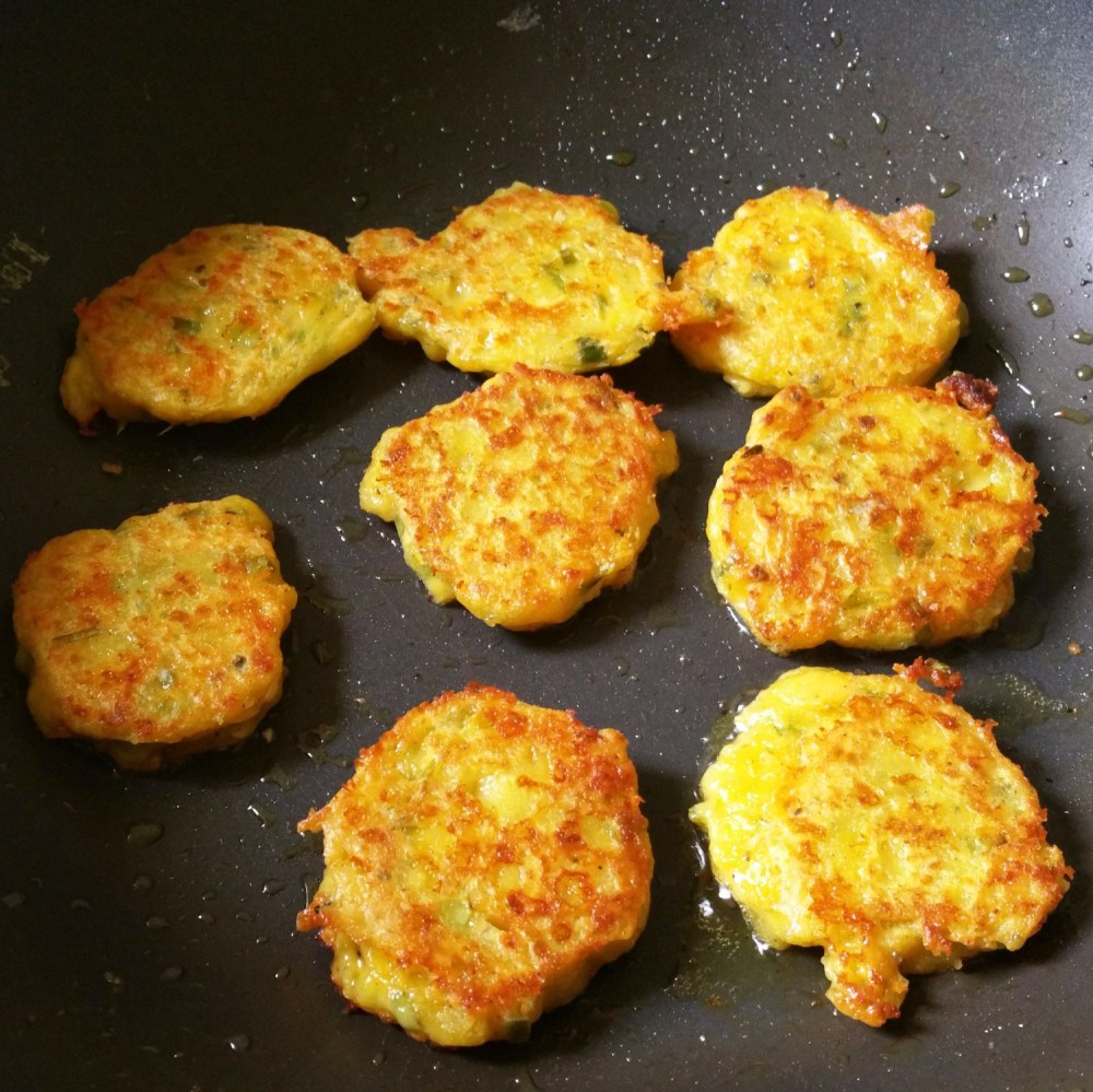Indian cheese fritters frying in a pan