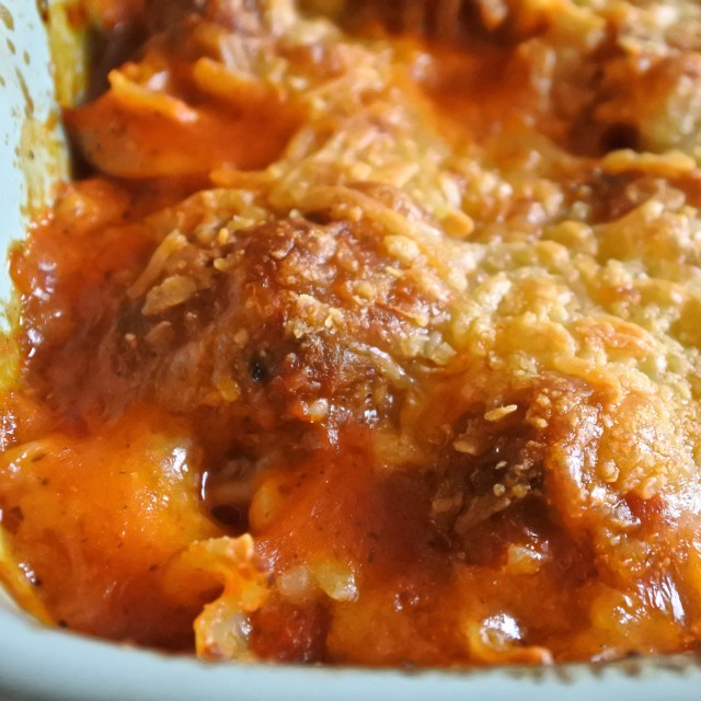 casserole dish of pasta and meatballs topped with melted cheese