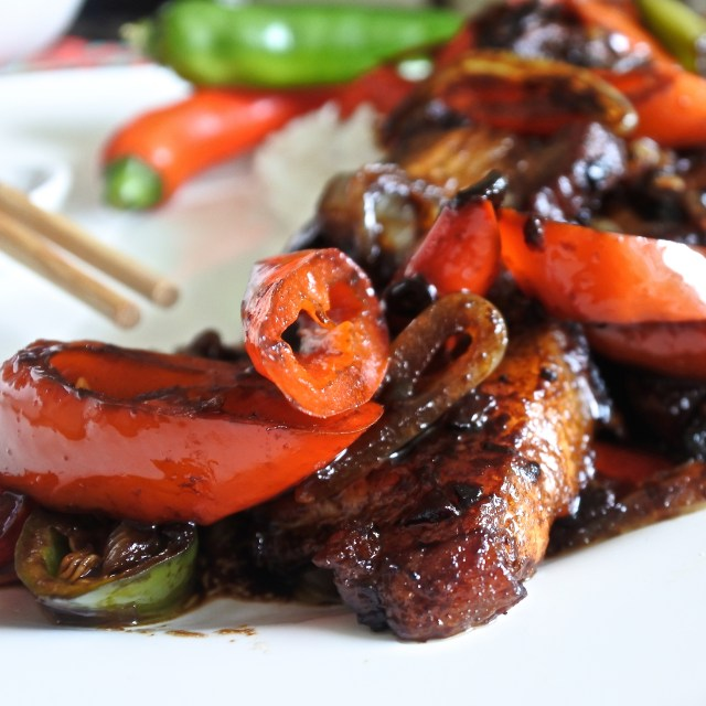 Pork belly slices stir fried in a Chinese black bean sauce with peppers and onions