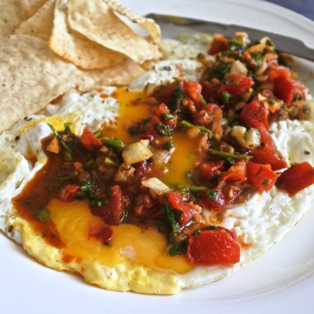 fresh chopped salsa atop over easy runny eggs with tortilla chips