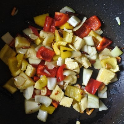 diced onions, bell peppers and pineapple frying in wok