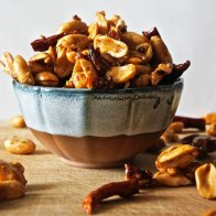 roasted peanuts in a bowl with red chiles