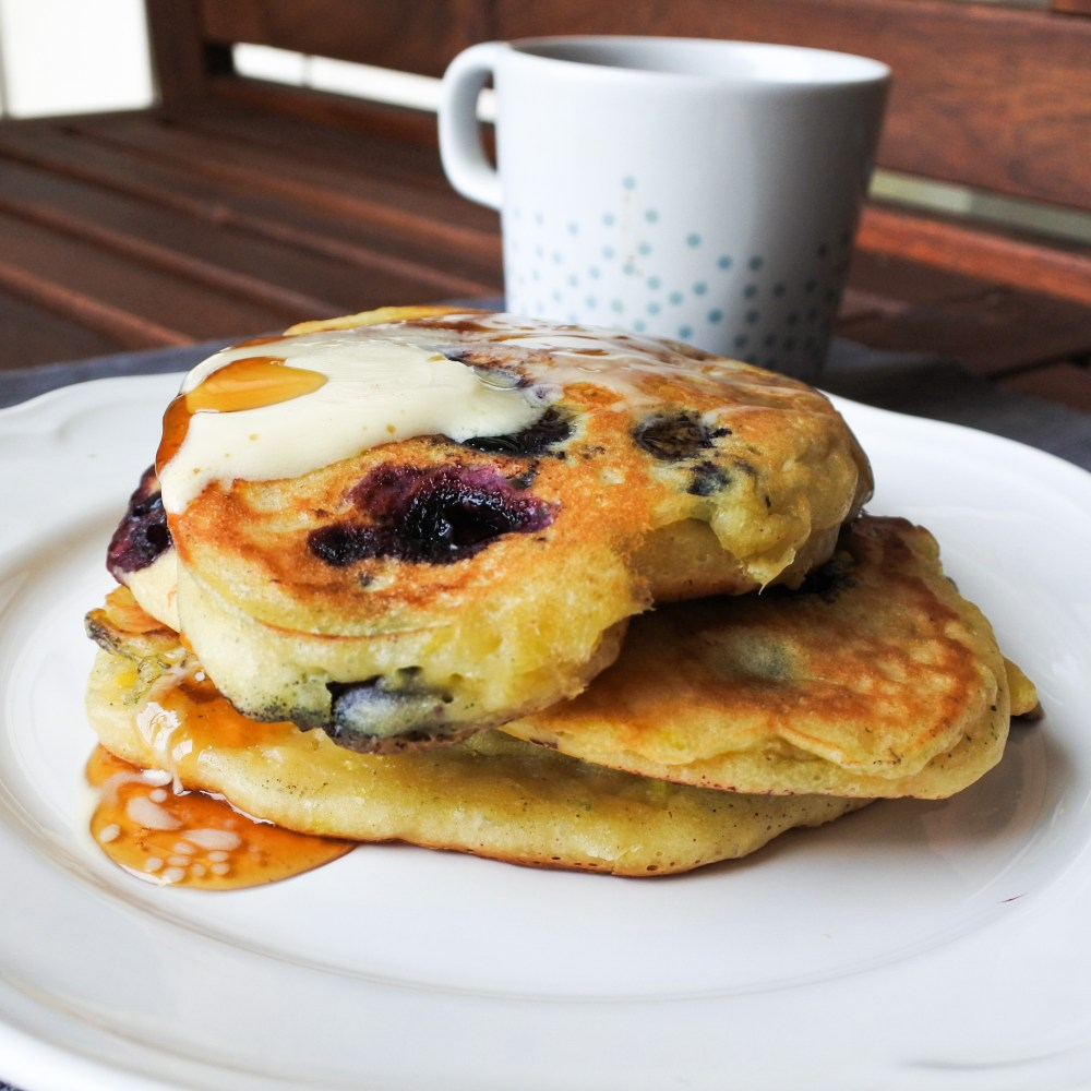blueberry pancakes on a plate with butter, honey and coffee