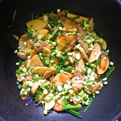 pork and pickled daikon stir fry garnished with chopped scallions