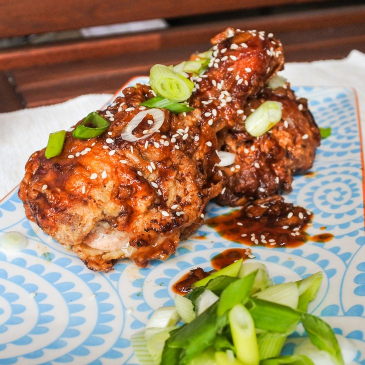 spicy fried chicken garnished with sesame seeds and scallions with pickled daikon