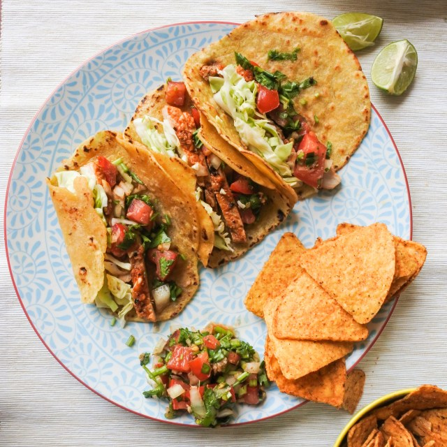 slow cooked pork, salsa and cabbage in tortillas on plate with lime and chips