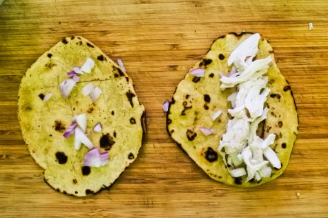 While enchilada sauce is cooking, start shredding the boiled chicken by tearing it apart with your hands. Be careful to let the chicken cool before shredding. To assemble the enchiladas, sprinkle the diced red onion in the center of the enchilada and top with shredded chicken.