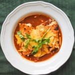 Enchiladas covered in red enchilada sauce and melted cheese
