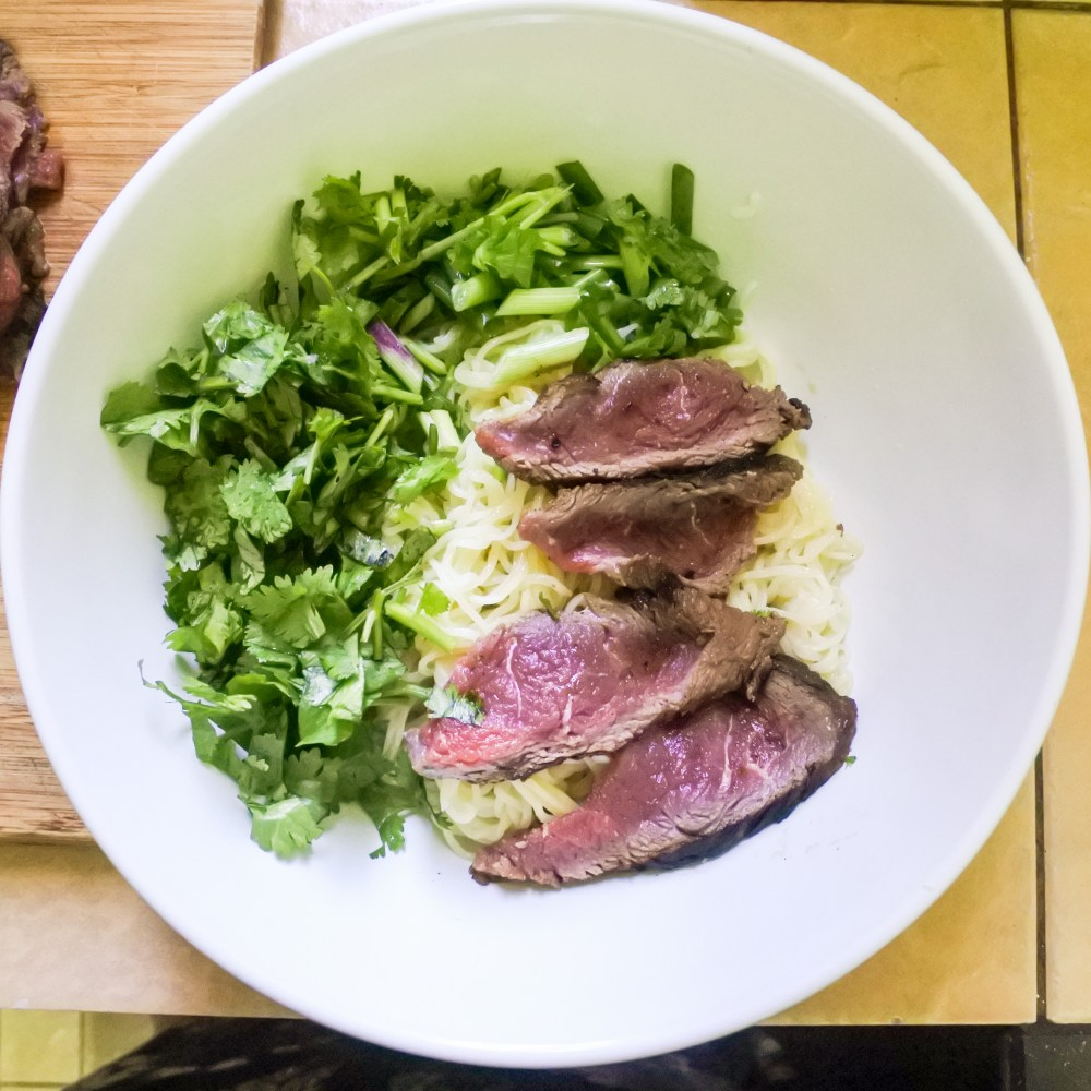 noodles, seared beef and chopped cilantro and scallions in bowl
