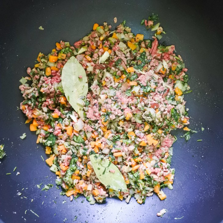 minced beef and diced vegetables cooking in a pan