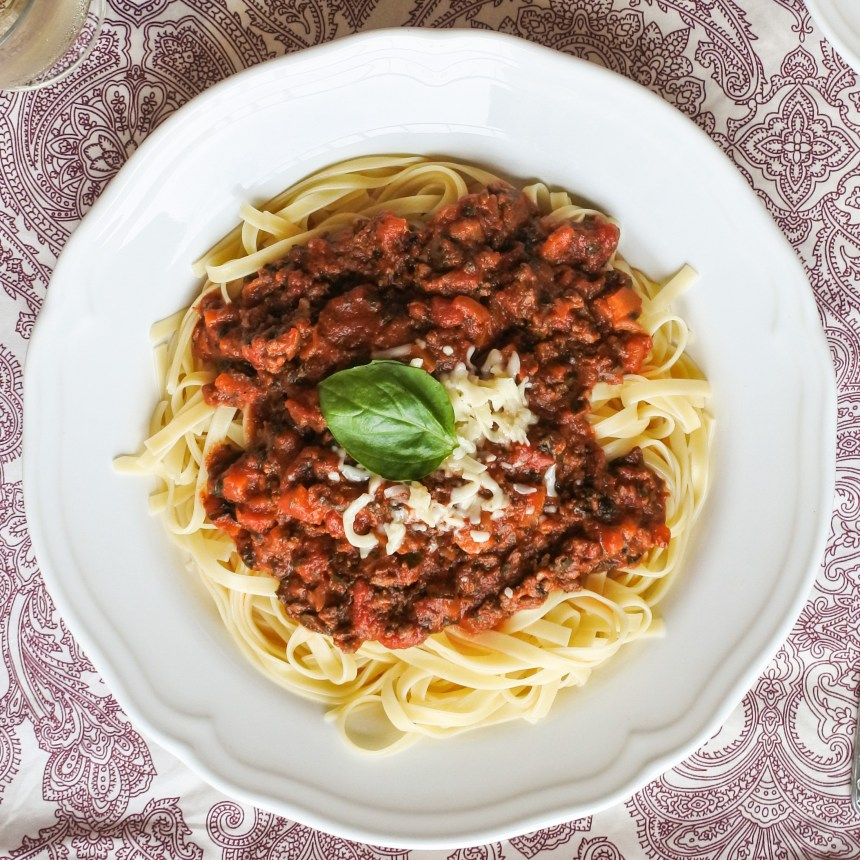 bolognese sauce over cooked fettuccine garnished with cheese and fresh basil