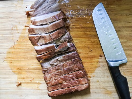 sliced meat on a cutting board with a knife