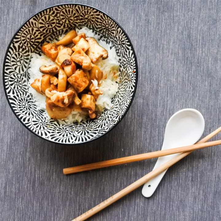 Tofu and Mushrooms in Soybean Sauce over steamed rice with chopsticks and spoon