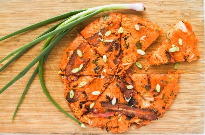 kimchi pancake and scallion on cutting board