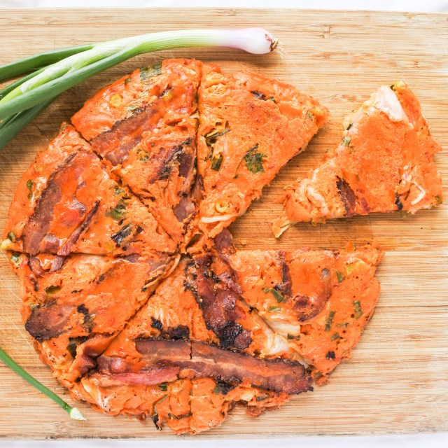 Bacon and kimchi pancake with scallion on cutting board