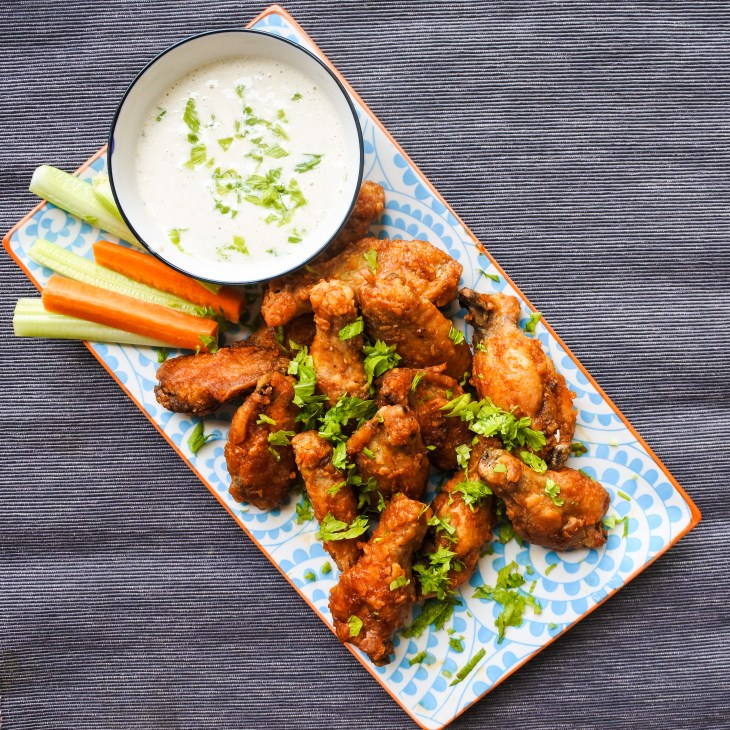 chicken wings on a plate with carrot and celery sticks and a ranch dipping sauce