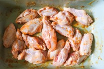 raw chicken wings tosses in butter and hot sauce in hot tray