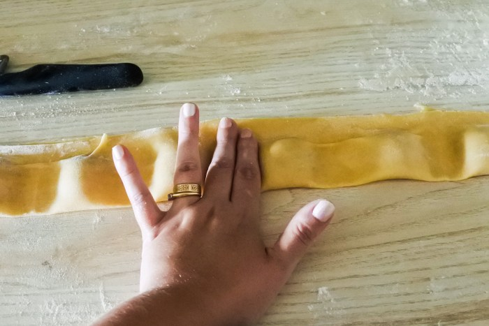 a hand pressing down pasta