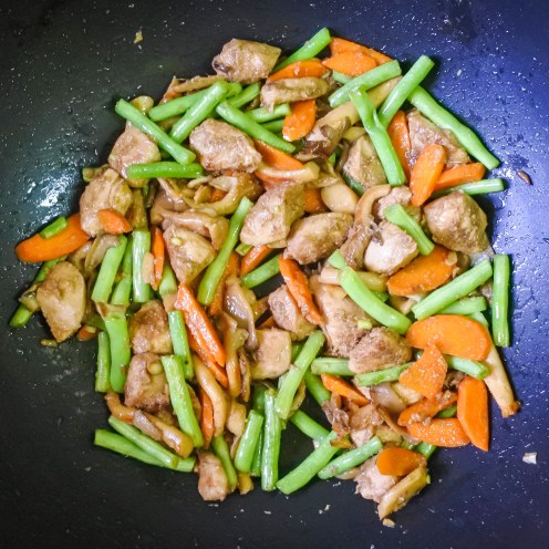 chicken and vegetables cooking in a wok