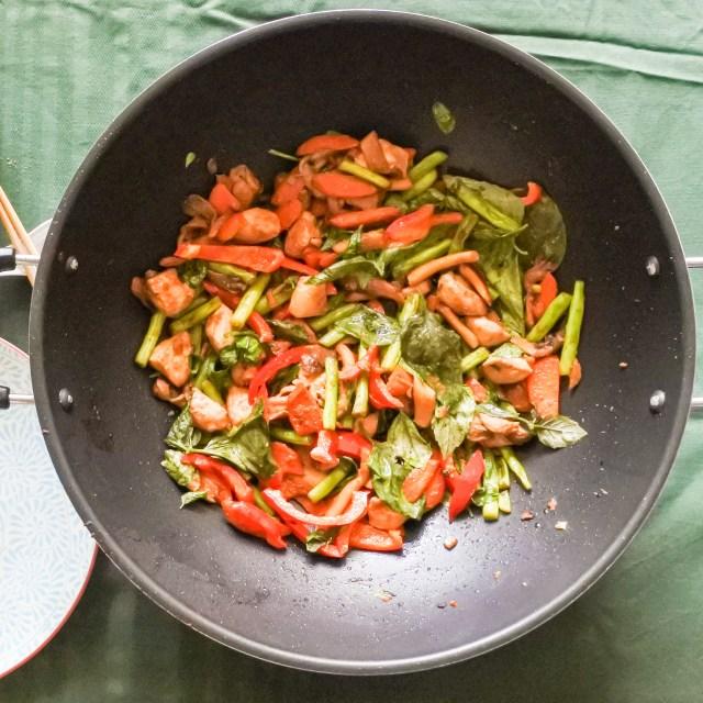 A wok with lemongrass chicken stir-fry inside