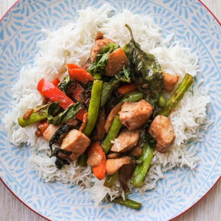 Lemongrass chicken stir-fry atop steamed jasmine rice on a plate