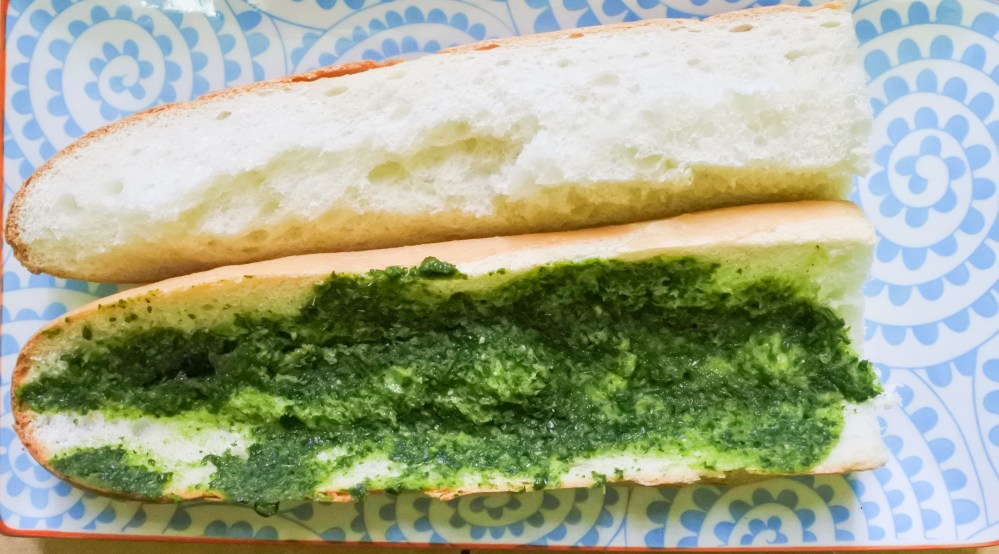 herb pesto spread on half of baguette
